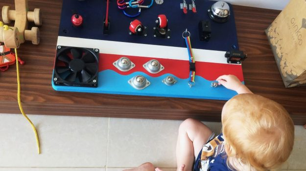 busyboard for two-year-old toddler with the bell, locks, latches and cool design. Little boy playing with activity board.