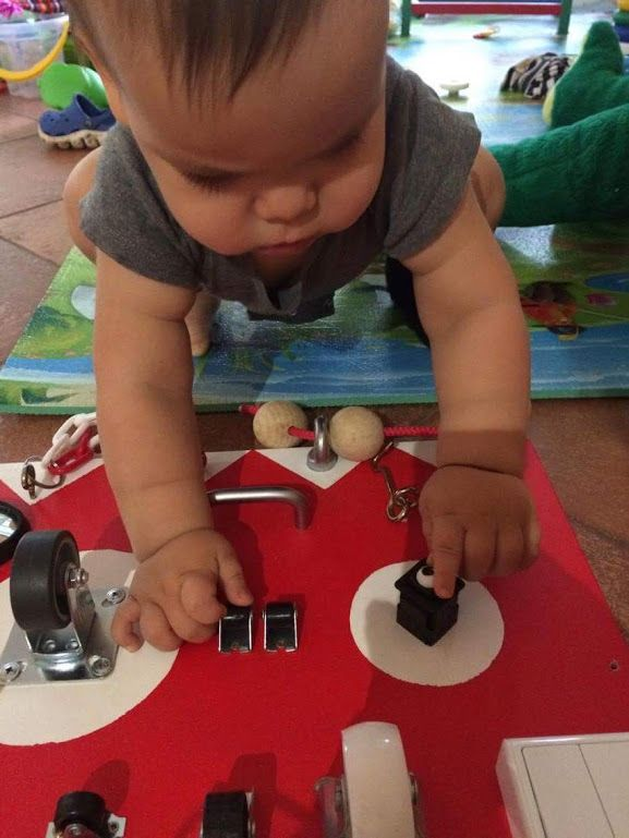 a one year old baby playing with a bright activity board