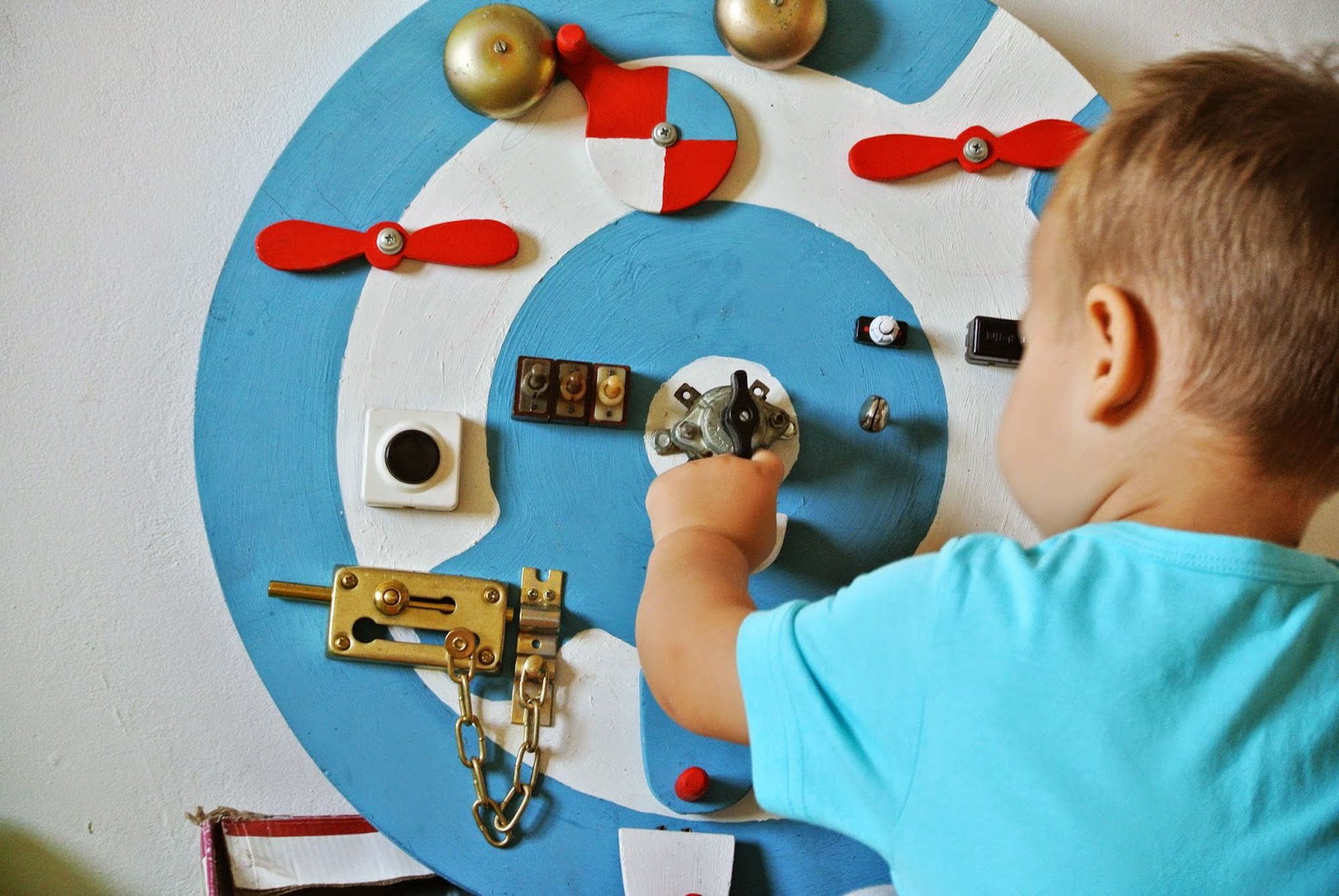 a toddler plays with a switch on round blue and white busy board