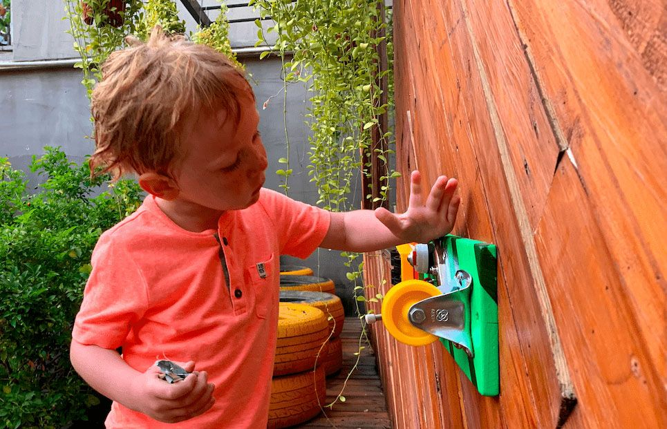 a kid playing with a busyboard sensory board activity board activity toy outside on the playground
